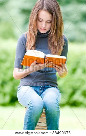 Serious Student Girl Sitting On Pile Of Books