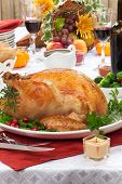picture of horn plenty  - Garnished roasted turkey on fall festival decorated table with horn of plenty and red wine - JPG