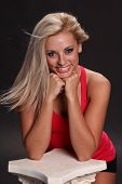 picture of wind blown  - An attractive smiling young female woman with long blond hair wearing a red tank top wind blown kneeling and isolated against black background - JPG