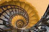 stock photo of spiral staircase  - Spiral staircase forged handhold and stone steps in old tower - JPG