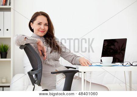 Zakelijke vrouw die op laptopcomputer op kantoor werkt