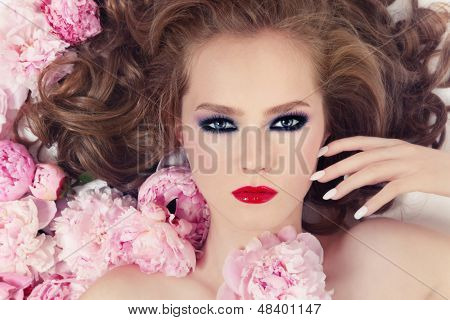 Portrait of young beautiful girl with stylish make-up and pink flowers in her hair
