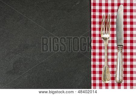 Cubiertos en una placa de la pizarra con un mantel a cuadros rojo