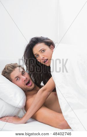 Embarrassed couple caught in the act in bed