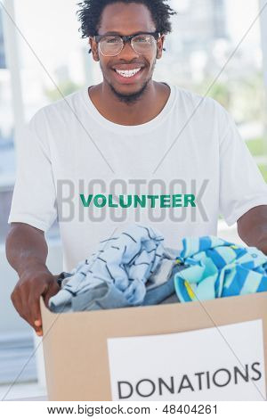 Cheerful man holding donation box full of clothes