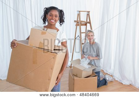 Young friends unpacking cardboard boxes in their new home and smiling at camera unpacking