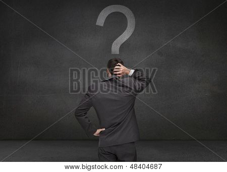 Rear view of a thoughtful businessman looking at a question mark
