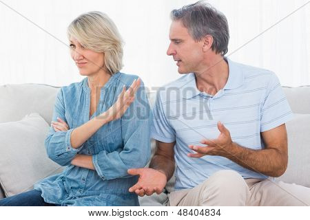 Man pleading with his wife after a fight at home on the couch