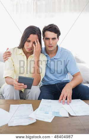 Stressed couple doing their accounts sat on a couch