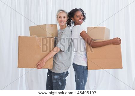 Happy friends standing back to back holding moving boxes looking at camera