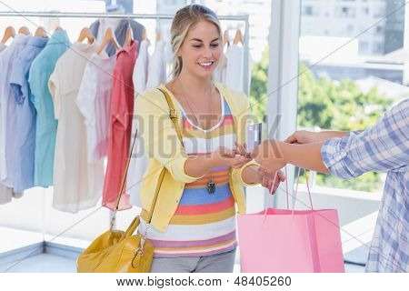 Attractive customer receiving her credit card and shopping bags