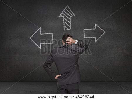 Thoughtful businessman looking at three arrows drawn on chalkboard