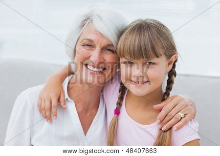 Cute girl and granny sitting on the couch in the living room