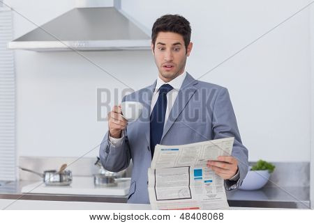 Businessman being astonished when reading the news in the kitchen at home