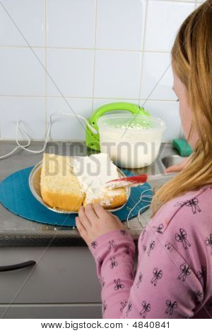 Girl Is Decorating A Cake With Whipped Cream