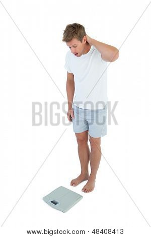 Man being astonished while looking at a weighing scale on white background