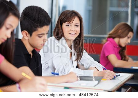 Portrait of teenage girl with male and female classmates sitting at desk in classroom