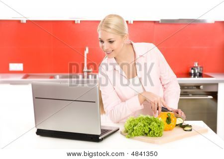 Woman With Laptop Preparing Food