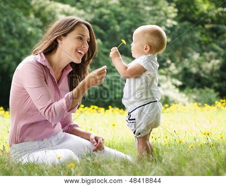 Mother Giving Child Flower In The Park