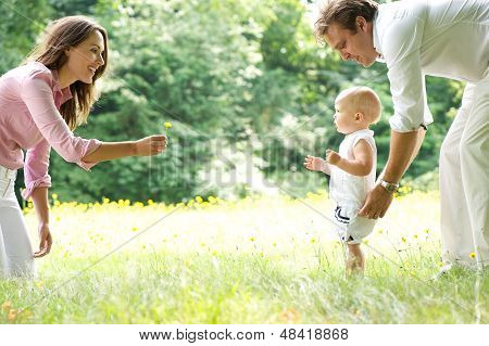 Happy Young Family Teaching Baby To Walk