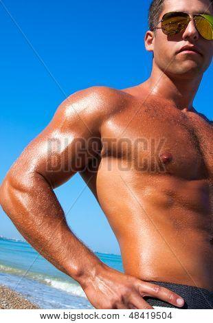 Muscular Brutal Man On The Beach