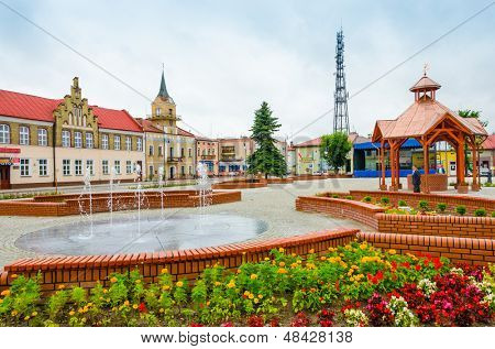 LUBACZOW, POLAND - JULY 14 : general view of market square with recently renovated thanks to EU funds town hall buildings and ancient well, Lubaczow, Poland on  July 14, 2013