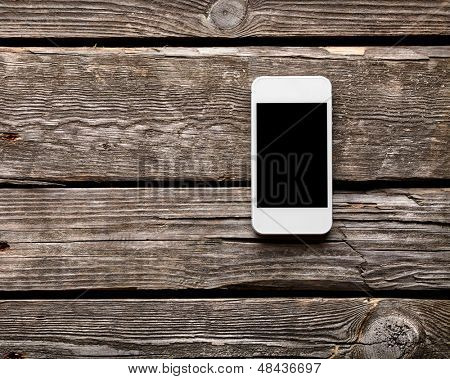 White smart phone with isolated screen on old wooden desk.
