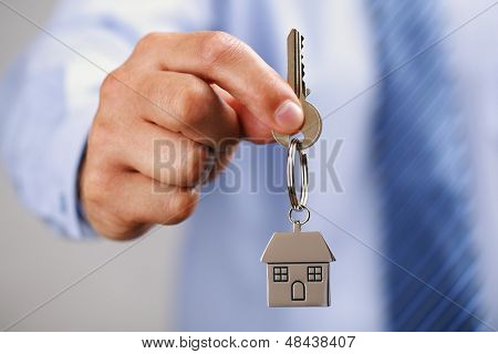 Holding out house keys on a  house shaped keychain