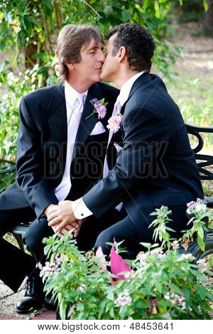 Handsome gay wedding couple kissing outdoors in the garden on their wedding day.