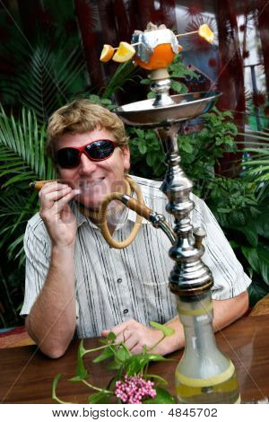Man Smoking A Hookah.