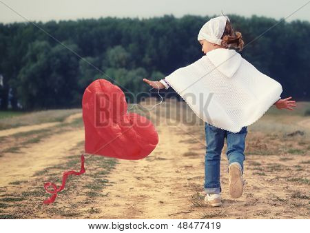Lovely little girl playing with red heart shaped balloon