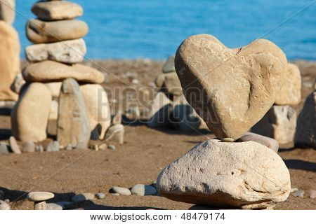 group of balanced stones with rock's heart at front view, pebbles stacks against blue sea