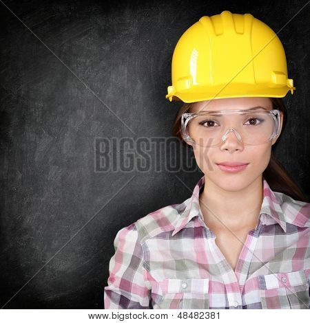 Serious woman construction worker, home owner in renovations or engineer face on black background texture with chalkboard for copy space. Young woman wearing safety glasses and hard hat.