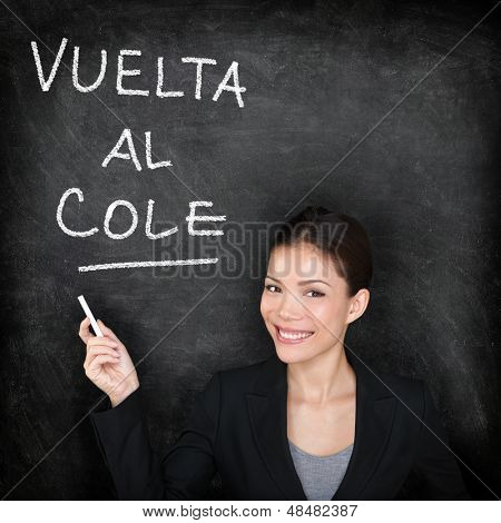 Vuelta al cole - Spanish teacher woman. Back to School written in Spanish on blackboard by female on chalkboard. Woman professor teaching Spanish language at university, high school or primary school.
