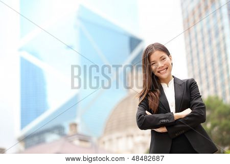 Young Asian business people business woman portrait outside. Businesswoman standing proud looking at camera in suit. Multiracial Chinese Asian / Caucasian female professional in central Hong Kong.
