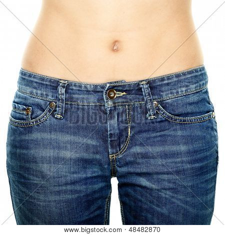 Woman waist wearing jeans. Weight loss stomach closeup. Skinny jeans on a healthy slim fit body.