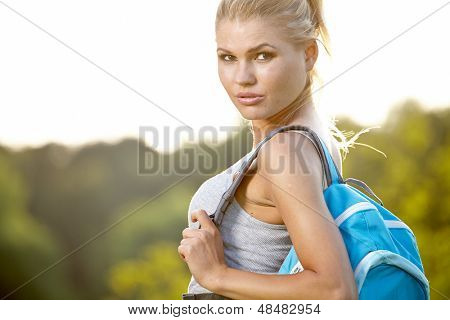 young blond woman hiking with scenery in thegreen landscape background