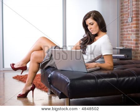 Young Woman On Laptop In A Modern Loft Or Home