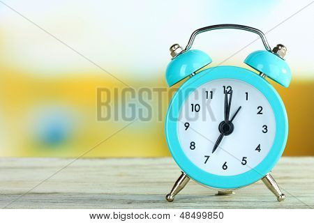 Alarm clock on table on bright background
