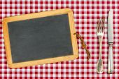 Empty blackboard with silverware on a checkered tablecloth