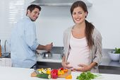 stock photo of pot-bellied  - Cheerful pregnant woman holding her belly in the kitchen with her husband cooking behind - JPG