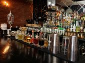 stock photo of liquor bottle  - Bitters and infusions on bar counter with blurred bottles in background - JPG