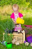 Little Girl Potting Up Seedlings In The Garden