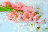 stock photo of gladiola  - Peach and white gladiola bouquet with wedding rings on a white satin pillow.