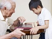 stock photo of grandpa  - asian grandpa and grandson playing chess game.