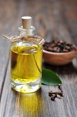 stock photo of toothache  - Oil of cloves in a glass bottle over wooden background - JPG