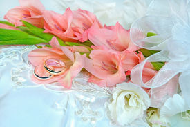 picture of gladiola  - Peach and white gladiola bouquet with wedding rings on a white satin pillow.