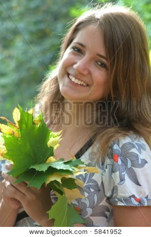 Young Pretty Woman With The Autumn Leaf