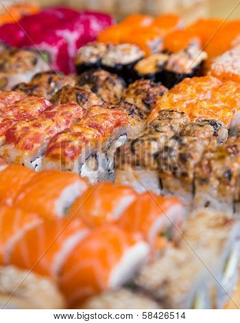 Assorted Sushi And Rolls On Wood Board In Dark Light