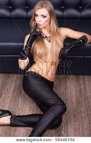sexy woman in black leather pants and glove sitting beside a black divan